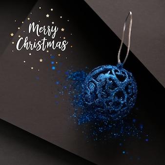 Frohe weihnachten schriftzug mit minimalistischer und einfacher komposition in matten schwarzer farbe weihnachtsgeschenkdekorationen auf schwarzem hintergrund