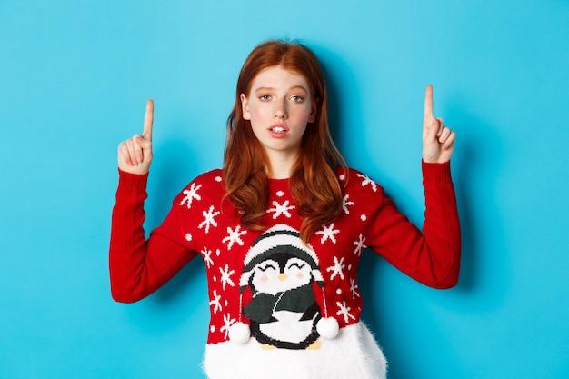 Frohe weihnachten. skeptisches und unlustiges rothaariges mädchen, das mit den fingern nach oben zeigt, logo mit widerstrebendem gesicht zeigt und auf blauem hintergrund steht.