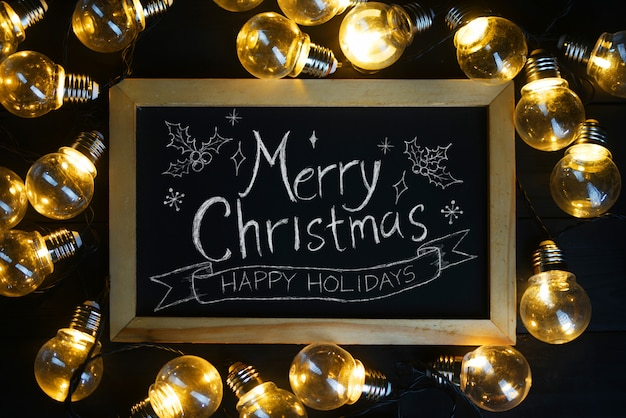 Frohe weihnachten-typografie auf tafel zwischen glühlampen auf schwarzem holz
