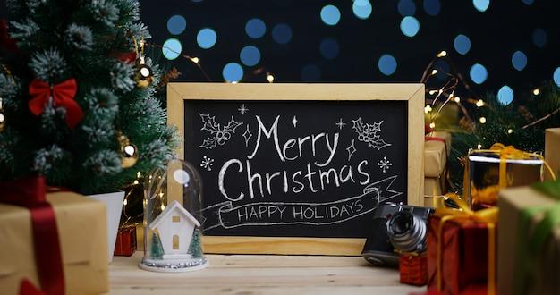Frohe weihnachten-typografie auf tafel zwischen weihnachtsdekoration