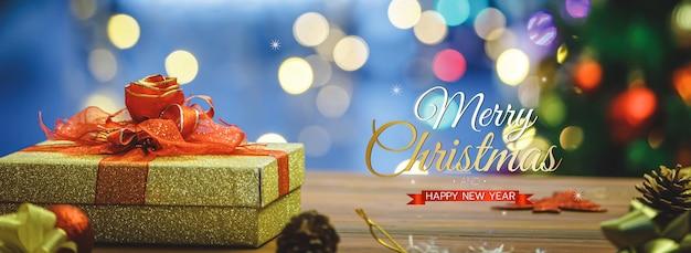 Frohe weihnachten und ein frohes neues jahr banner für kopf oder cover der social media website oder fanseite dekorativ. goldene geschenkbox mit roter fliege mit segnendem weihnachtstext und hellem bokeh.