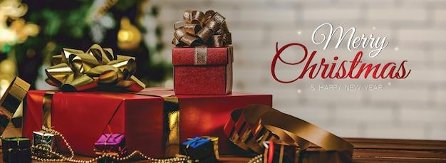 Frohe weihnachten und ein frohes neues jahr banner für kopf oder cover der social media website oder fanseite dekorativ. stapel von geschenkboxen auf backsteinmauerhintergrund mit weihnachtssegen beschriftet den gebrauchsfertigen text.