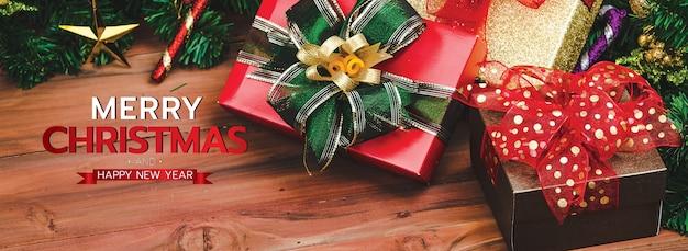 Frohe weihnachten und ein frohes neues jahr banner für kopf oder cover der social media website oder fanseite dekorativ. stapel von geschenkboxen auf holz hintergrund mit weihnachtssegen buchstaben text gebrauchsfertig.