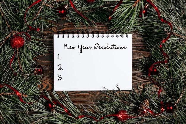 Frohe weihnachten und ein frohes neues jahr konzept mit geschenkboxen, spielzeug und notizbuch mit text neujahrsvorsätze