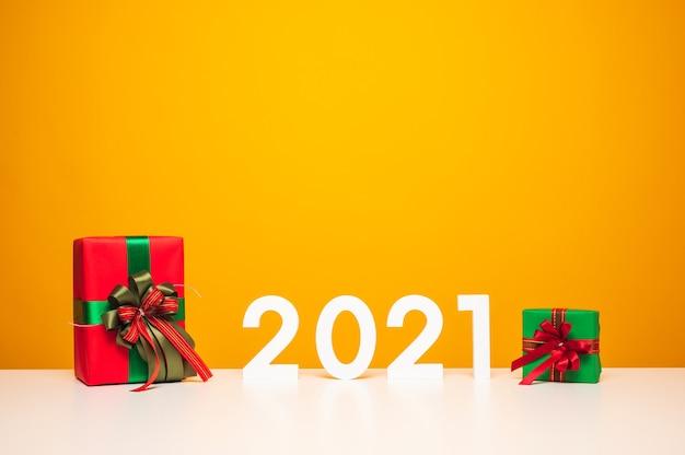 Frohe weihnachten und ein frohes neues jahr modell auf weißem tisch und gelb