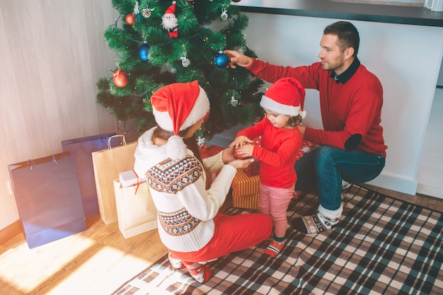 Frohe weihnachten und ein glückliches neues jahr. attraktives bild der netten und netten familie. sie schmücken weihnachtsbaum. junge frau hält spielzeug mit kleinem mädchen. mann setzt blaues spielzeug auf baum.