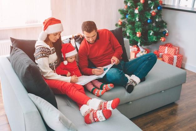 Frohe weihnachten und ein glückliches neues jahr. bild von den erwachsenen, die mit bleistiften im malbuch zeichnen. sie sind konzentriert, ruhig und friedlich. kleines mädchen schau dir das an. sie trägt rote kleidung und einen hut.