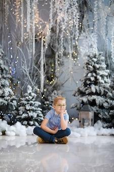 Frohe weihnachten und ein glückliches neues jahr! charmanter kleiner junge sitzt zu hause