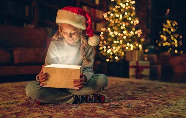 Frohe weihnachten und ein glückliches neues jahr! charmantes kleines mädchen sitzt zu hause mit offener geschenkbox. magisches licht von innen.