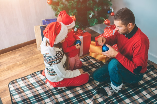 Frohe weihnachten und ein glückliches neues jahr. ernsthafte und konzentrierte familienmitglieder halten zwei blaue spielzeuge in der hand. sie werden sie auf den weihnachtsbaum legen. familie ist auf decke und an kisten mit geschenken.