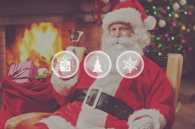 Frohe weihnachten und ein glückliches neues jahr! fröhlicher weihnachtsmann sitzt auf seinem stuhl und läutet eine glocke mit kamin und weihnachtsbaum im hintergrund