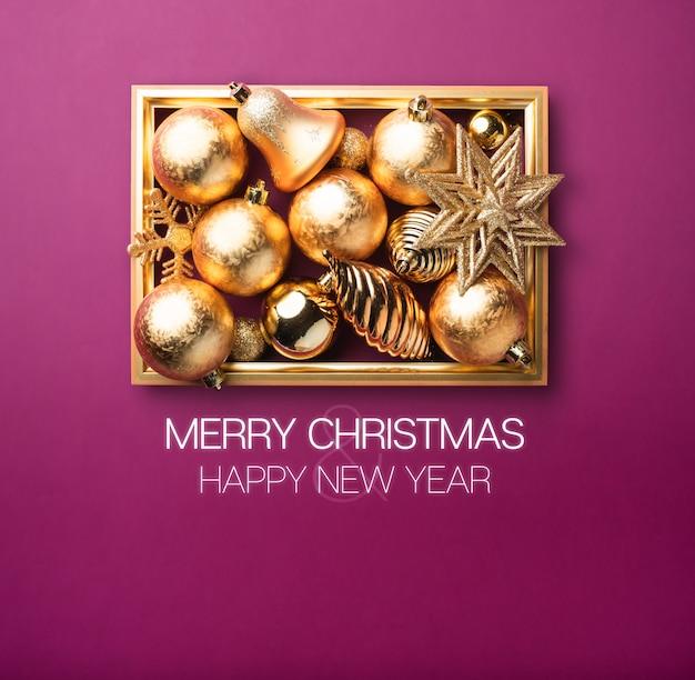Frohe weihnachten und ein glückliches neues jahr. glänzender goldweihnachtsdekorationsball und -stern mit goldenem rahmen im purpur