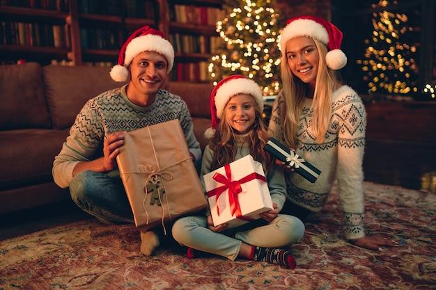 Frohe weihnachten und ein glückliches neues jahr! glückliche familie wartet auf das neue jahr in santa claus hüte tauschen geschenke miteinander aus.