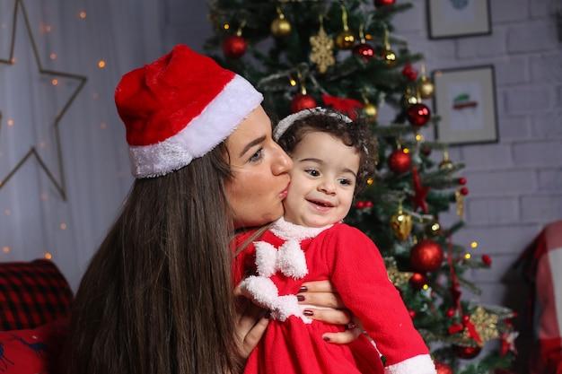 Frohe weihnachten und ein glückliches neues jahr! porträt eines emotionalen kindes in einem kostüm des neuen jahres mit ihrer mutter im verzierten raum.