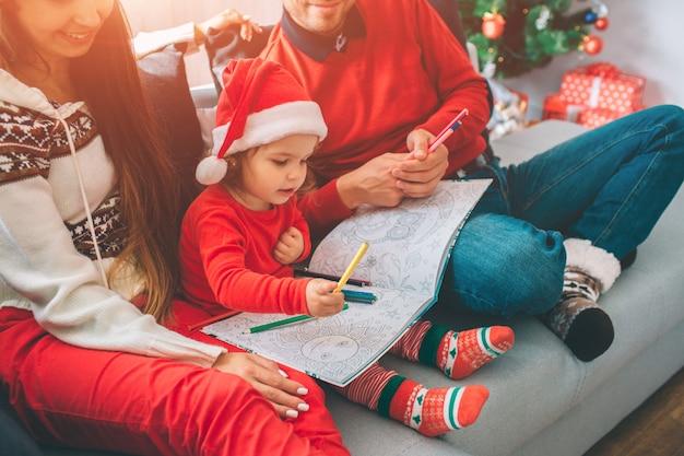 Frohe weihnachten und ein glückliches neues jahr. schneiden sie ansicht von den eltern, die auf sofa mit ihrem kind sitzen. kind hält färbung und bleistifte darauf. mädchen malen damit. junger mann hält auch einige bleistifte.
