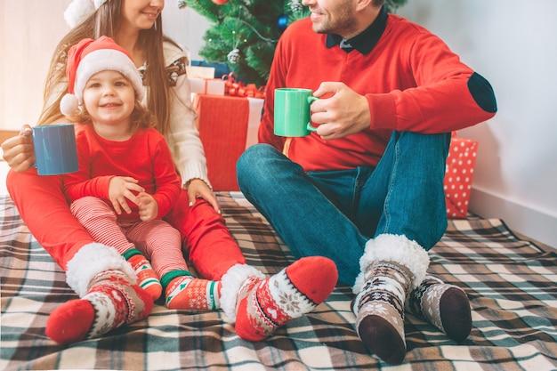 Frohe weihnachten und ein glückliches neues jahr. schnittansicht von mann und frau sitzen auf decke mit ihrem kind. sie halten tassen und schauen sich an. sie lächeln. kinderblick und kamera und lachen.
