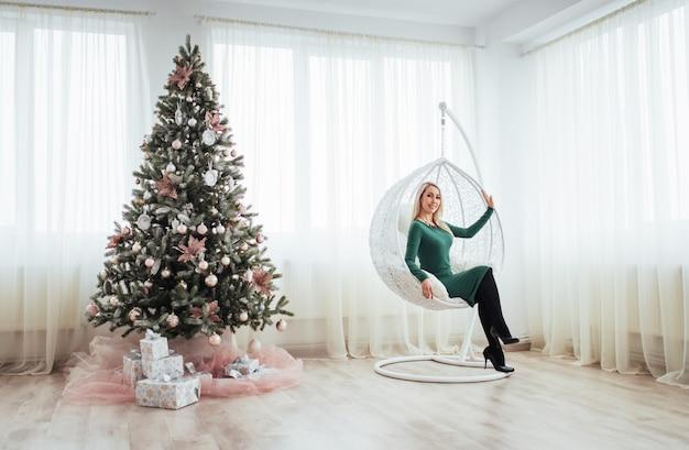Frohe weihnachten und ein glückliches neues jahr. schöne blonde frau in einem grünen kleid, das im stuhl verschoben am baum sitzt