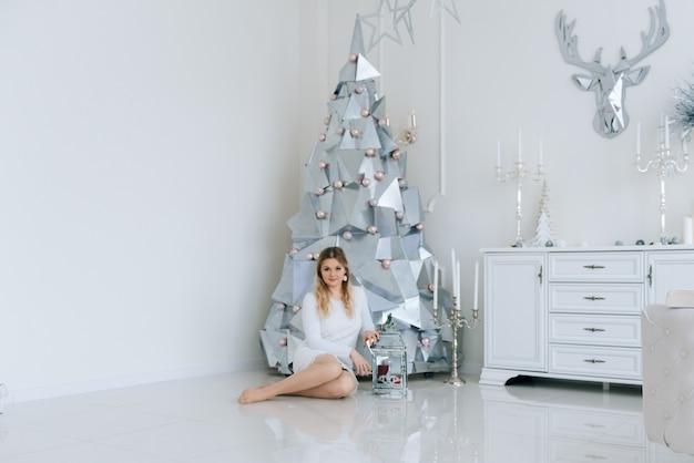 Frohe weihnachten und ein glückliches neues jahr. schönes mädchen, das mit einem kerzenhalter nahe dem modernen silbernen metallweihnachtsbaum sitzt