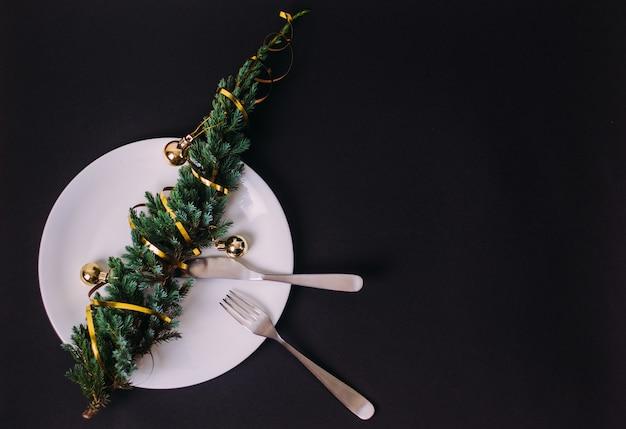 Frohe weihnachten und ein glückliches neues jahr! weihnachtsbaum auf einer weißen platte. schwarzes, copyspace. für menü und restaurants für die feiertage.