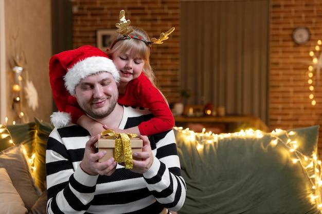 Frohe weihnachten und ein glückliches neues jahr. weihnachtsgeschenk überraschung. ein kleines lächelndes tochtermädchen, das den vater zurück umarmt und das geschenk drinnen zu hause hält, das für den urlaub dekoriert ist. gut aussehender mann hält geschenkbox