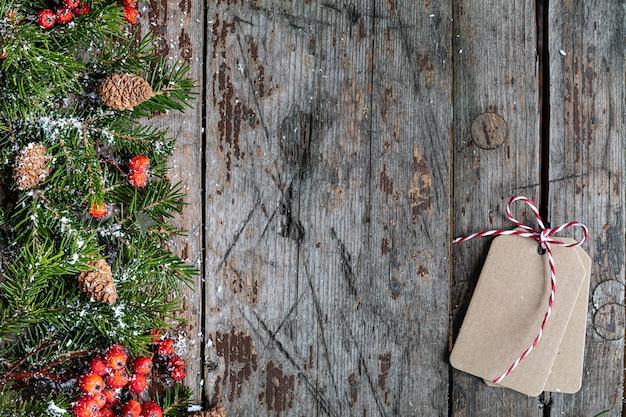Frohe weihnachten und frohe feiertage grußkarte, rahmen, fahne. neujahr. frohes neues jahr karte mit schnee auf hölzernem hintergrund. winterweihnachtsfeiertagsthema. flach liegen. speicherplatz kopieren