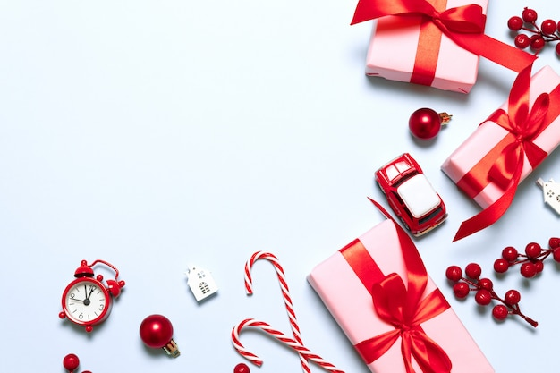 Frohe weihnachten und frohe feiertage zusammensetzung mit weihnachtsgeschenken, rotem dekor, autospielzeug, zuckerstange und funkeln