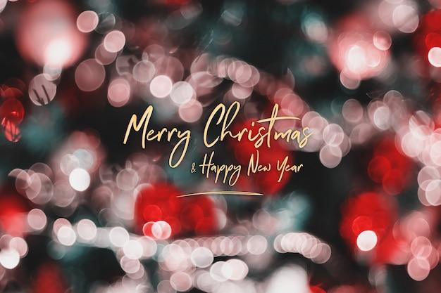 Frohe weihnachten und guten rutsch ins neue jahr auf unschärfedekorationsball und lichterkette auf weihnachtsbaum