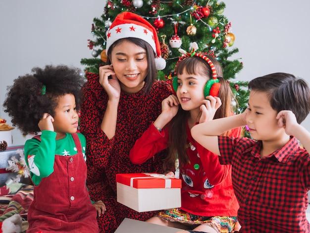 Frohe weihnachten und happy holiday mit internationalen menschen, kinder feiern weihnachten im haus