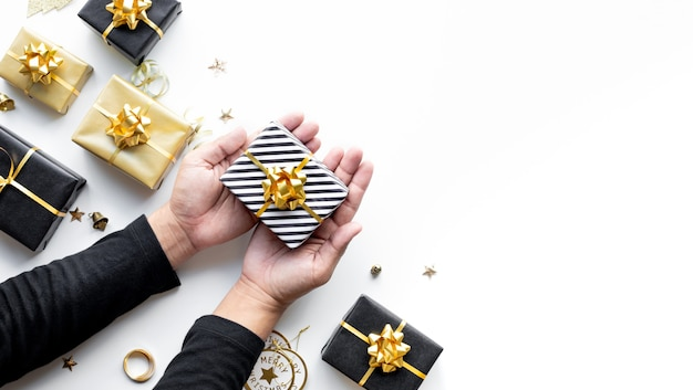 Frohe weihnachten und neujahrsfeierkonzepte mit personenhand, die geschenkbox hält