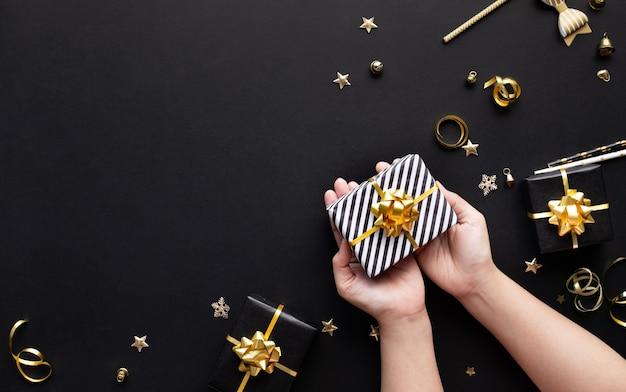 Frohe weihnachten und neujahrsfeierkonzepte mit personenhand, die geschenkbox und verzierung in gold hält