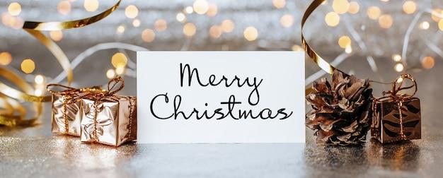 Frohe weihnachten und neujahrskonzept mit geschenkboxen und grußkarte mit text frohe weihnachten