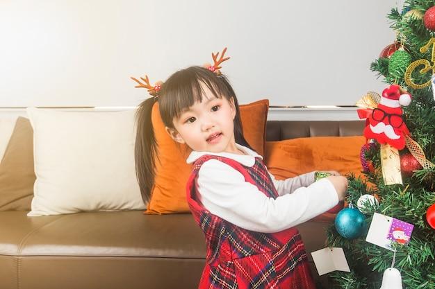 Frohe weihnachten und schöne feiertage! feiertags- und kindheitskonzept. glückliches kleines lächelndes mädchen mit weihnachtsgeschenkbox.