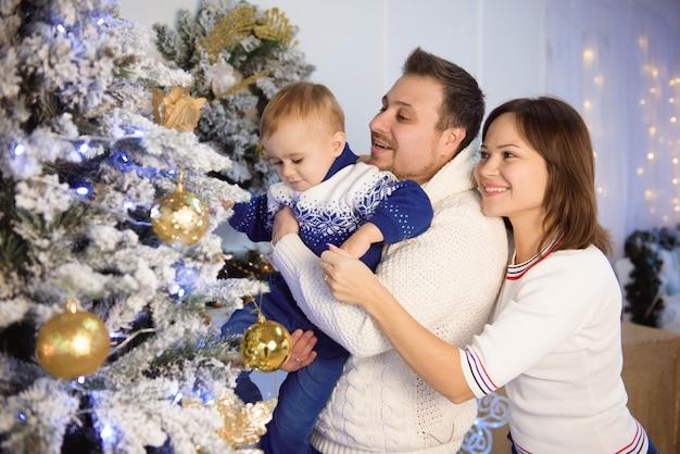 Frohe weihnachten und schöne feiertage. freundliche mamma, vati und sohn, die geschenke austauschen.
