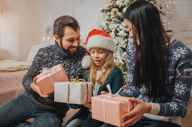 Frohe weihnachten und schöne feiertage fröhliche mutter, vater und ihr süßes tochtermädchen tauschen geschenke aus.