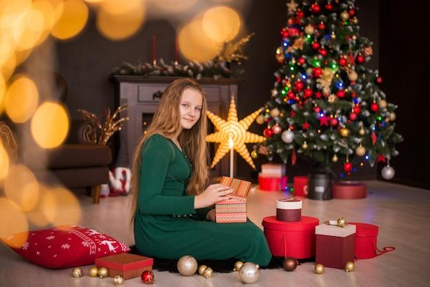 Frohe weihnachten und schöne feiertage. fröhliches süßes jugendlich mädchen, das geschenke öffnet.