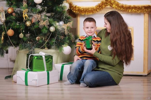 Frohe weihnachten und schöne feiertage. hübsche junge mutter mit ihrem lustigen kleinen sohn nahe weihnachtsbaum mit geschenkboxen drinnen.