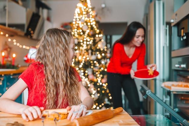Frohe weihnachten und schöne feiertage. mutter und ihre töchter kochen weihnachtsplätzchen auf der küche
