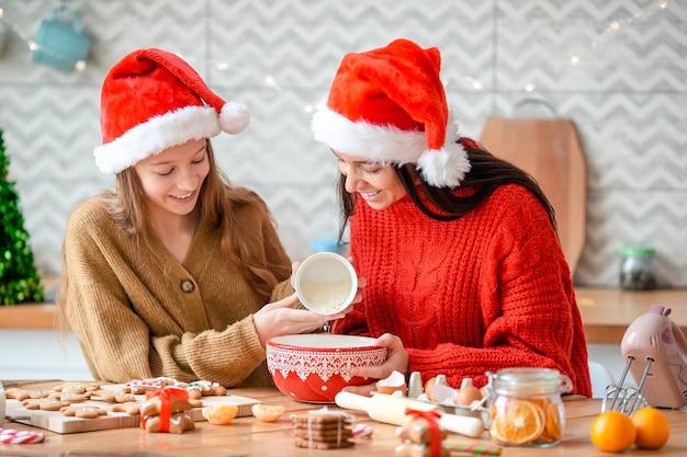 Frohe weihnachten und schöne feiertage. mutter und tochter kochen kekse.