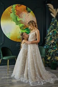 Frohe weihnachten und schöne feiertage. mutter und tochter schmücken den weihnachtsbaum drinnen. mutter und tochter im gleichen kleid. porträt liebevolle familie hautnah.