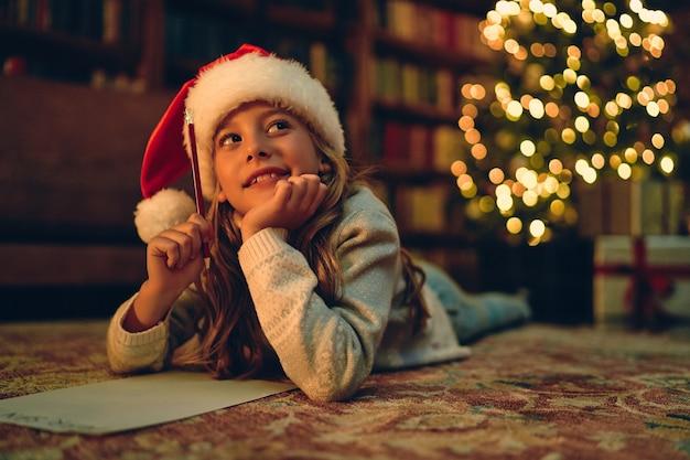 Frohe weihnachten und schöne feiertage! nettes kleines kind mädchen schreibt den brief an den weihnachtsmann in der nähe von weihnachtsbaum drinnen.