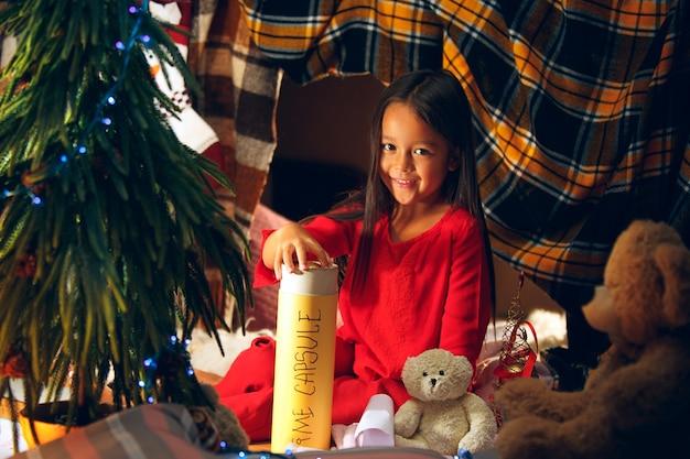 Frohe weihnachten und schöne feiertage. nettes kleines kind mädchen schreibt den brief an den weihnachtsmann in der nähe von weihnachtsbaum zu hause drinnen. urlaub, kindheit, winter, feierkonzept