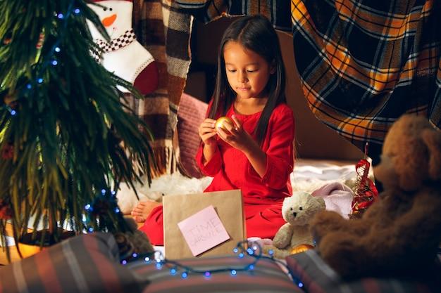 Frohe weihnachten und schöne feiertage. nettes kleines kind mädchen schreibt den brief an den weihnachtsmann in der nähe von weihnachtsbaum