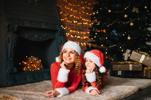 Frohe weihnachten und schöne feiertage! schöne mutter mit kleiner tochter in weihnachtskostümen verbringen zeit zusammen nahe dem weihnachtsbaum.