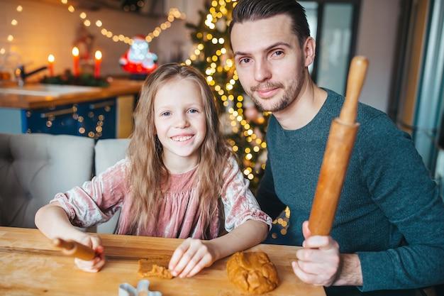 Frohe weihnachten und schöne feiertage. vater und kleine tochter kochen weihnachtsplätzchen zu hause