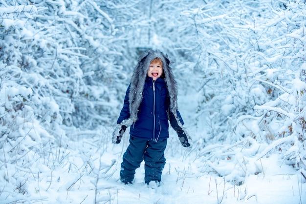 Frohe weihnachten und schöne feiertage winterkind kleines kind im schneefeld, das naturwinter genießt...