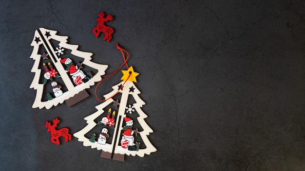 Frohe weihnachtsbaumspielwaren auf einem schwarzen hintergrund.