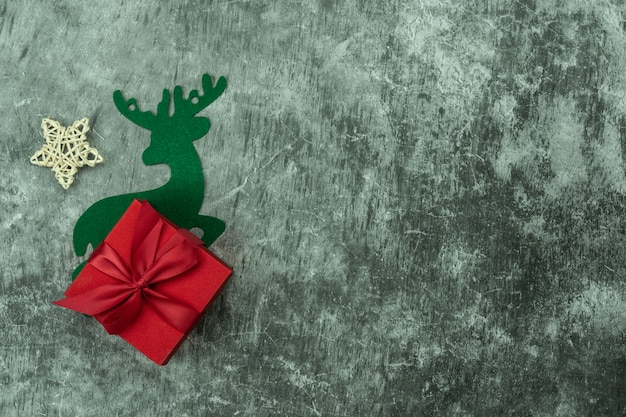 Frohe weihnachtsdekorationen. flache verlegung wesentlicher unterschied objekte geschenkbox & rentier auf modernen zement