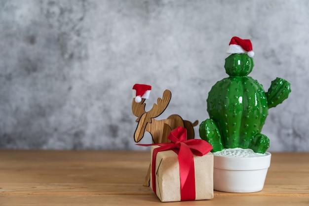 Frohe weihnachtsdekorationen. geschenkbox mit kaktus mit rengegenstand