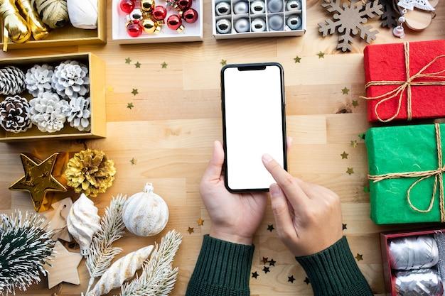 Frohe weihnachtskonzepte mit der jungen frau unter verwendung des smartphones mit leerem bildschirm