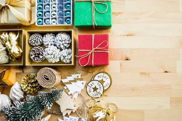 Frohe weihnachtskonzepte mit geschenkboxgeschenk und verzierungselement auf holz